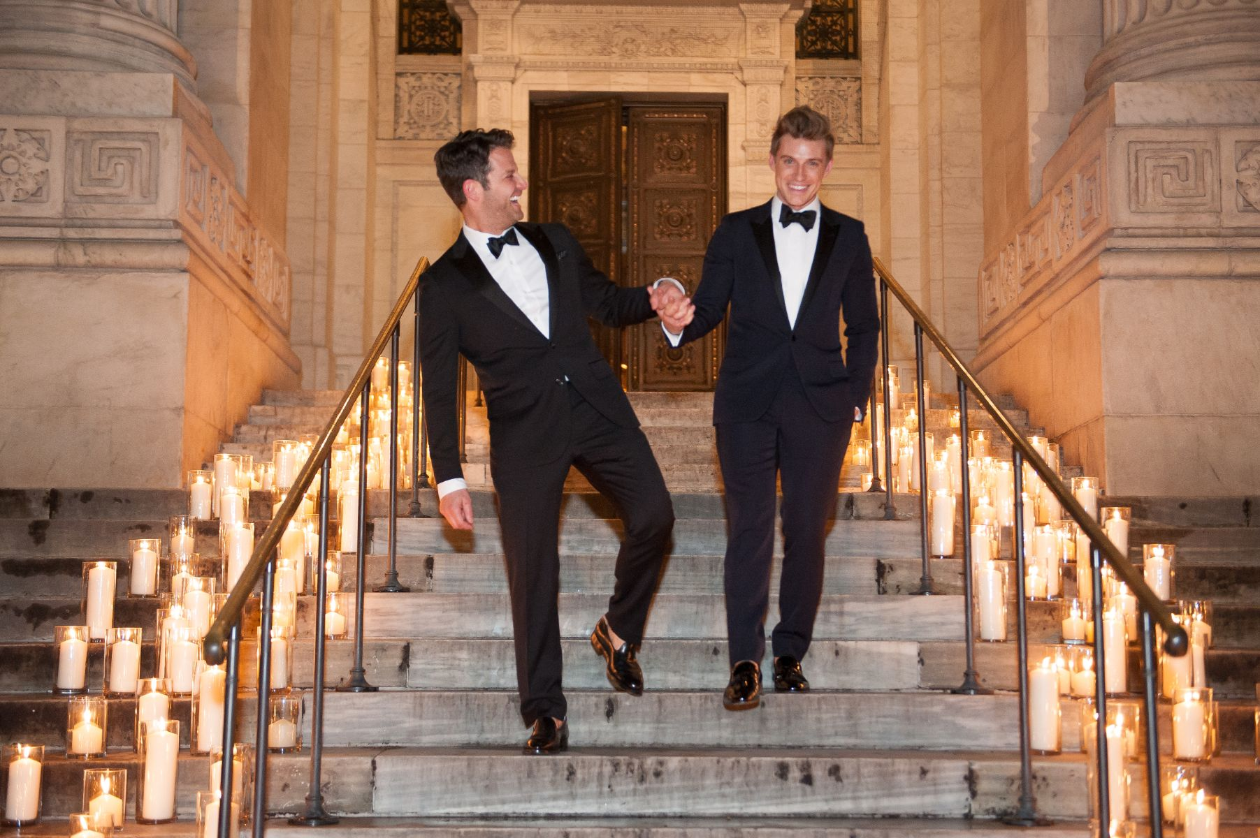 Two grooms hold hands at their wedding.
