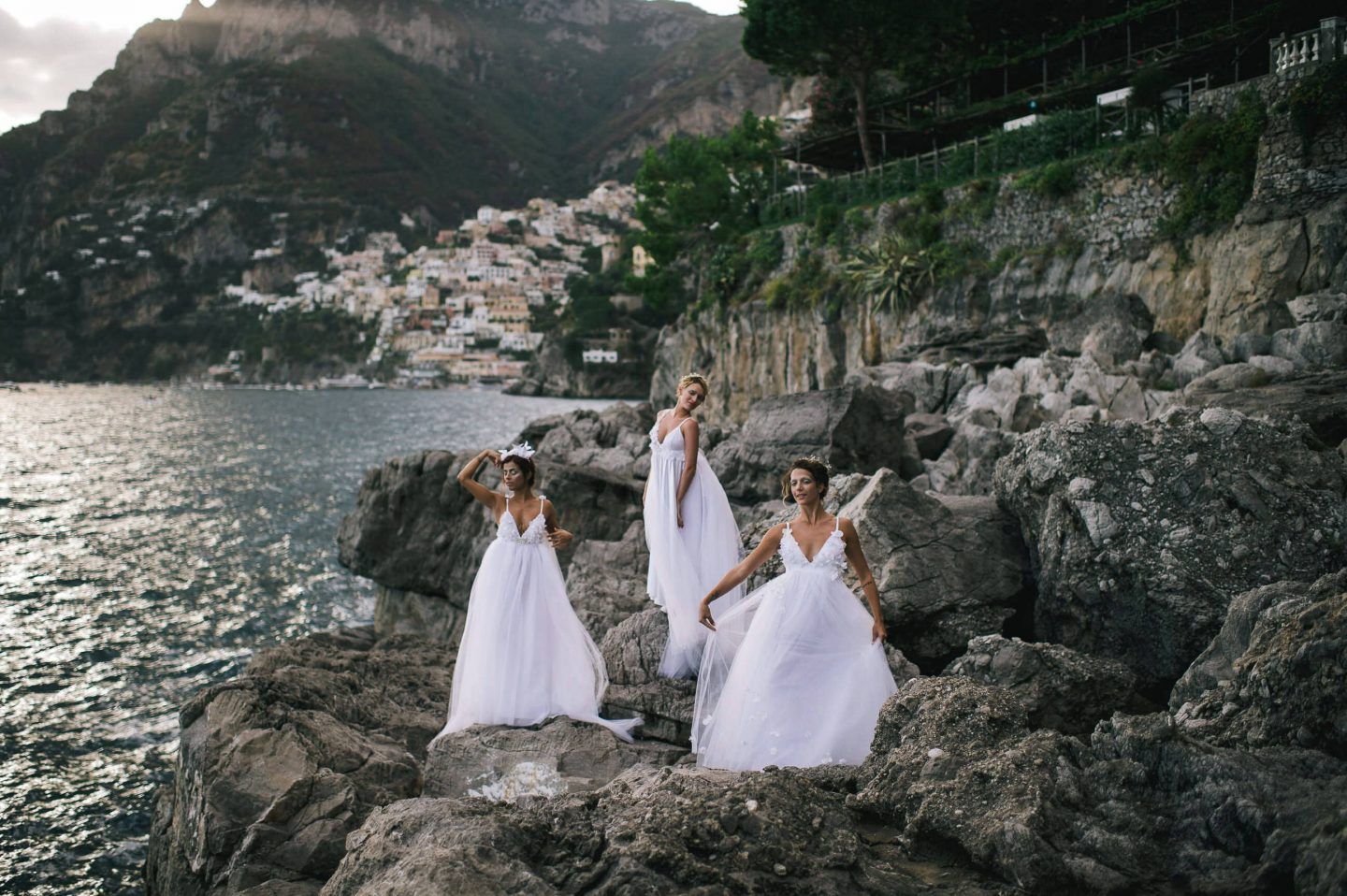 Women in white dresses on the rocks to greet guest for Midsummer Night's Eve-themed white welcome party at this Positano wedding weekend in Villa Tre Ville | Photo by Gianni di Natale