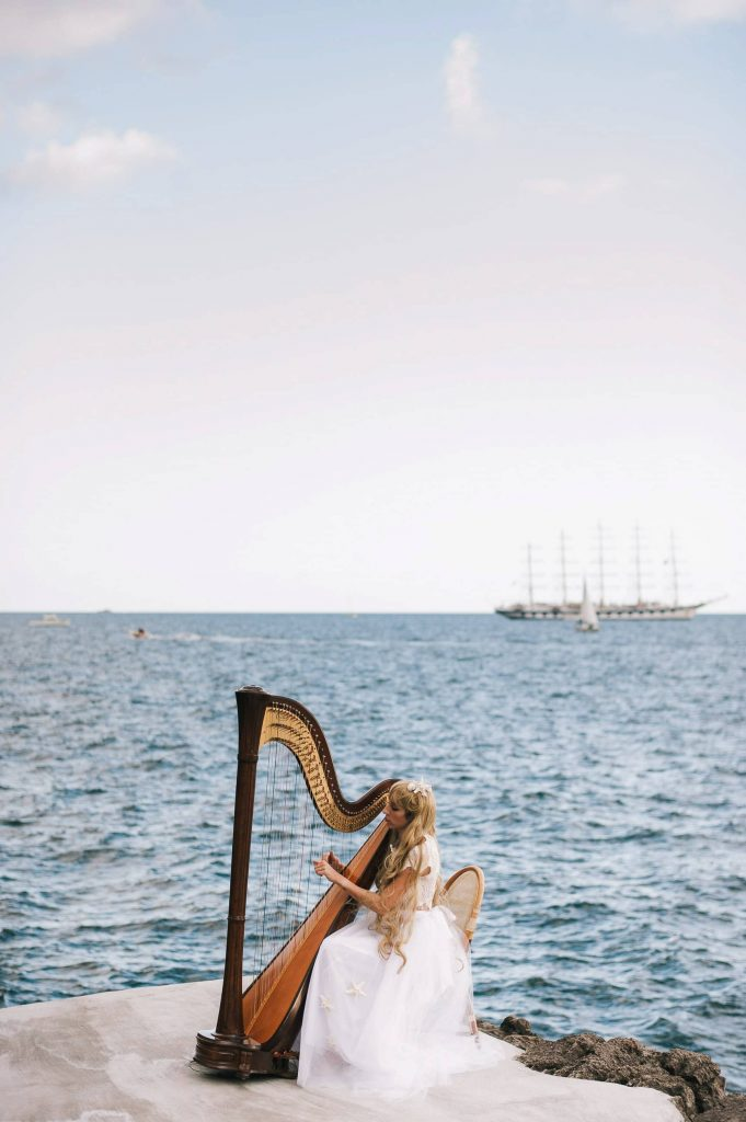 Harpist for Midsummer Night's Eve-themed white welcome party at this Positano wedding weekend in Villa Tre Ville | Photo by Gianni di Natale