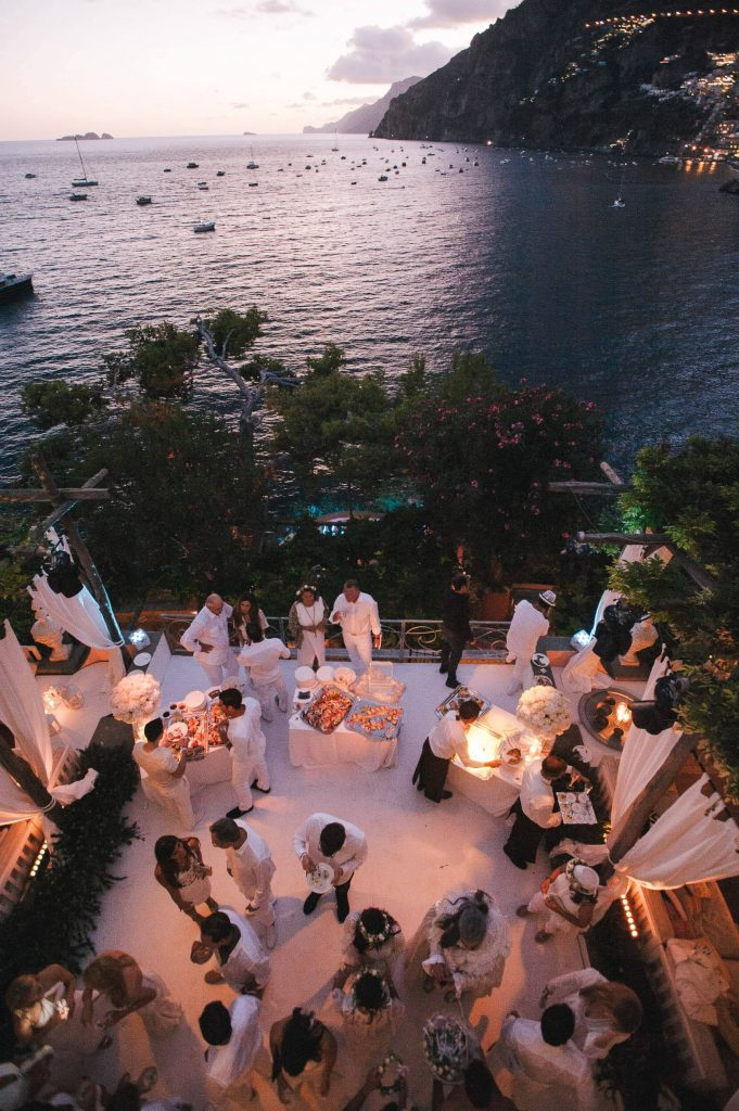 Guests at night at the Midsummer Night's Eve-themed white welcome party at this Positano wedding weekend in Villa Tre Ville | Photo by Gianni di Natale