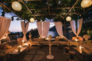 Outdoor lounge at night at the Midsummer Night's Eve-themed white welcome party at this Positano wedding weekend in Villa Tre Ville | Photo by Gianni di Natale