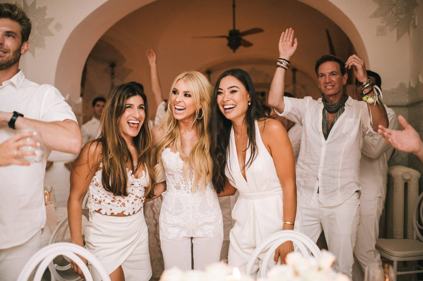 Bride with guests at the Midsummer Night's Eve-themed white welcome party at this Positano wedding weekend in Villa Tre Ville | Photo by Gianni di Natale