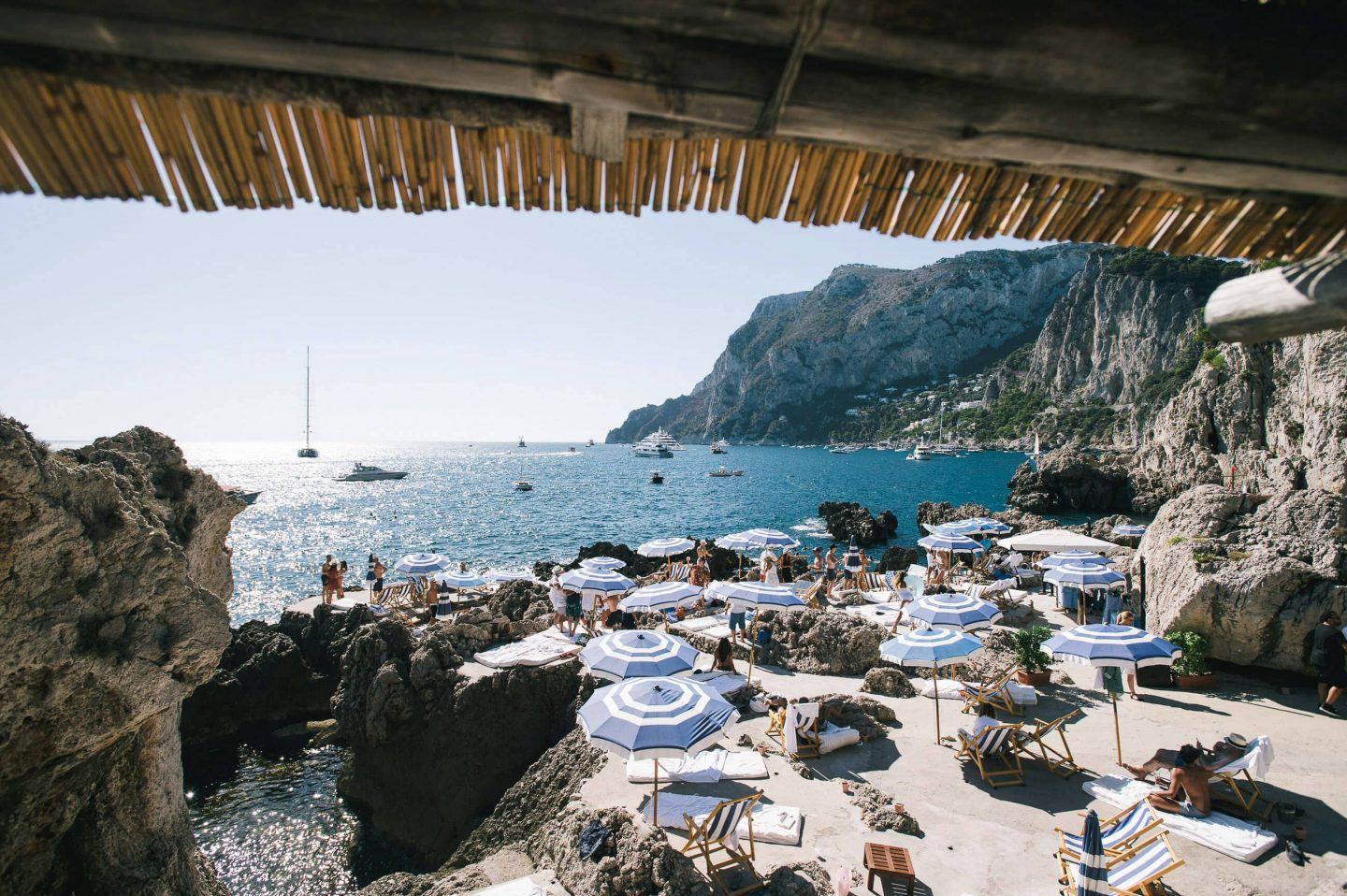 Guests under blue umbrellas at La Fontelina in Capri at this Positano wedding weekend in Villa Tre Ville | Photo by Gianni di Natale