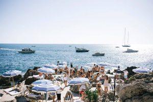 Guests under blue umbrellas La Fontelina in Capri at this Positano wedding weekend in Villa Tre Ville | Photo by Gianni di Natale