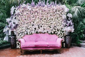White flower wall with pink velvet couch at this Positano wedding weekend in Villa Tre Ville | Photo by Gianni di Natale