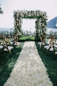 Floral arch with aisle made of white petals at this Positano wedding weekend in Villa Tre Ville | Photo by Gianni di Natale