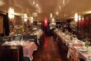 Tables covered in L'Atelier Rouge hand-dyed linens from India at this 40th surprise birthday party at Beatrice Inn in West Village | Photo by Darren Ornitz