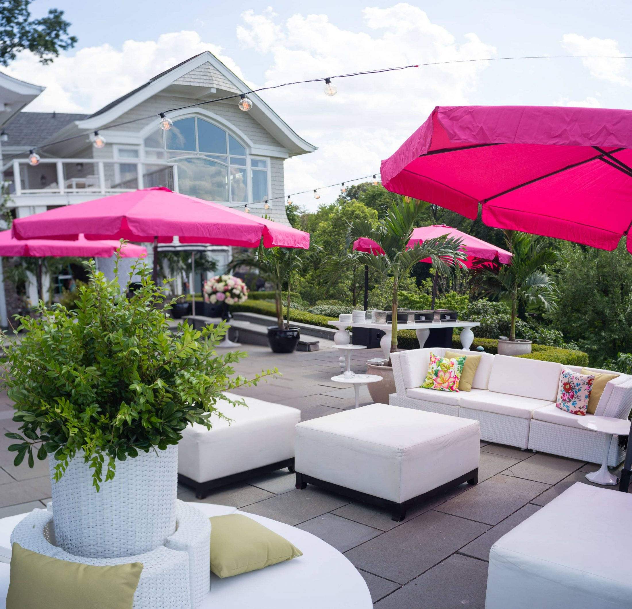 Lounge area with pink umbrellas at this South Beach-inspired first birthday pool party in the Hamptons | Photo by Cava Photo