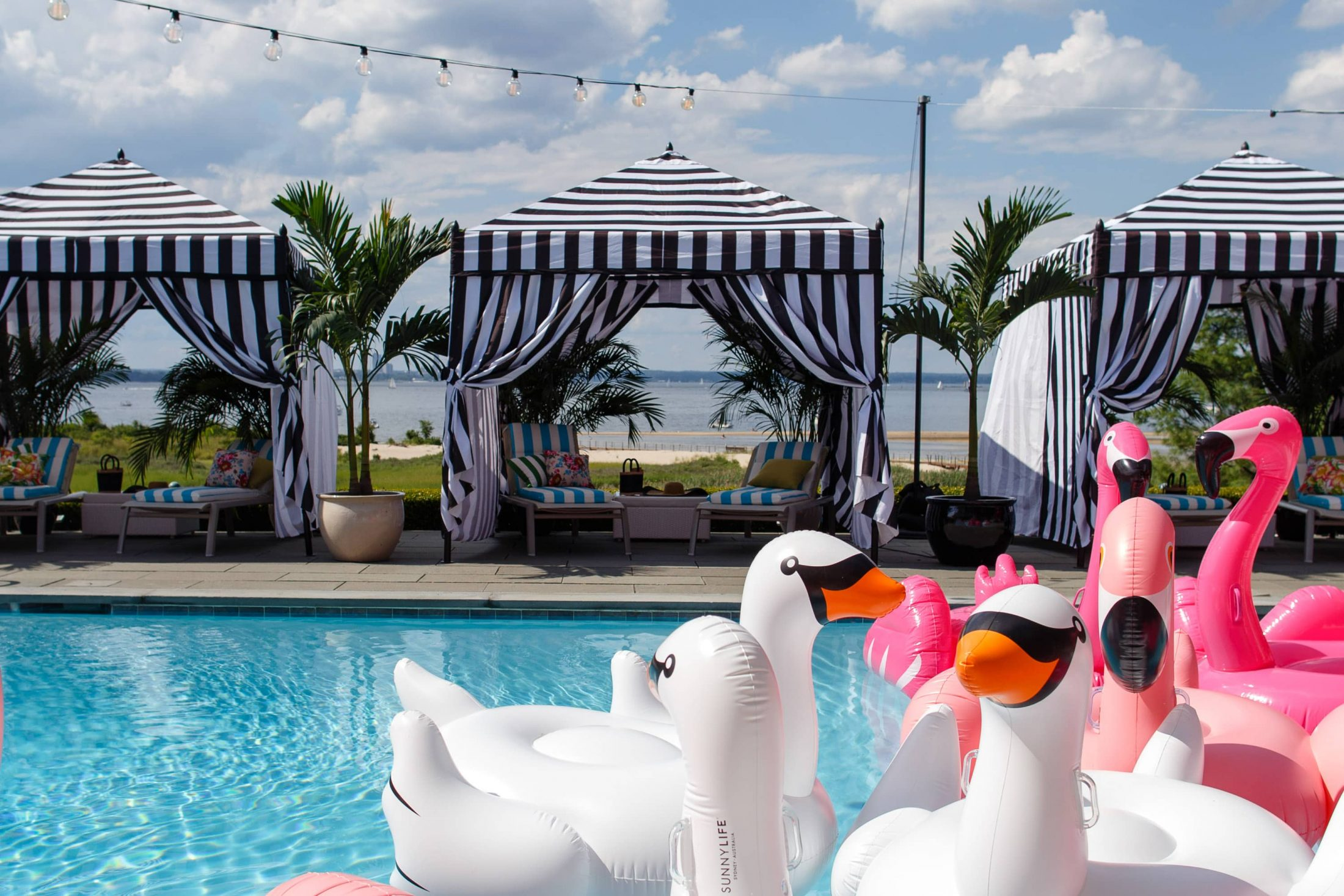 Striped tents and flamingo and swan pool floats at this South Beach-inspired first birthday pool party in the Hamptons   Photo by Cava Photo