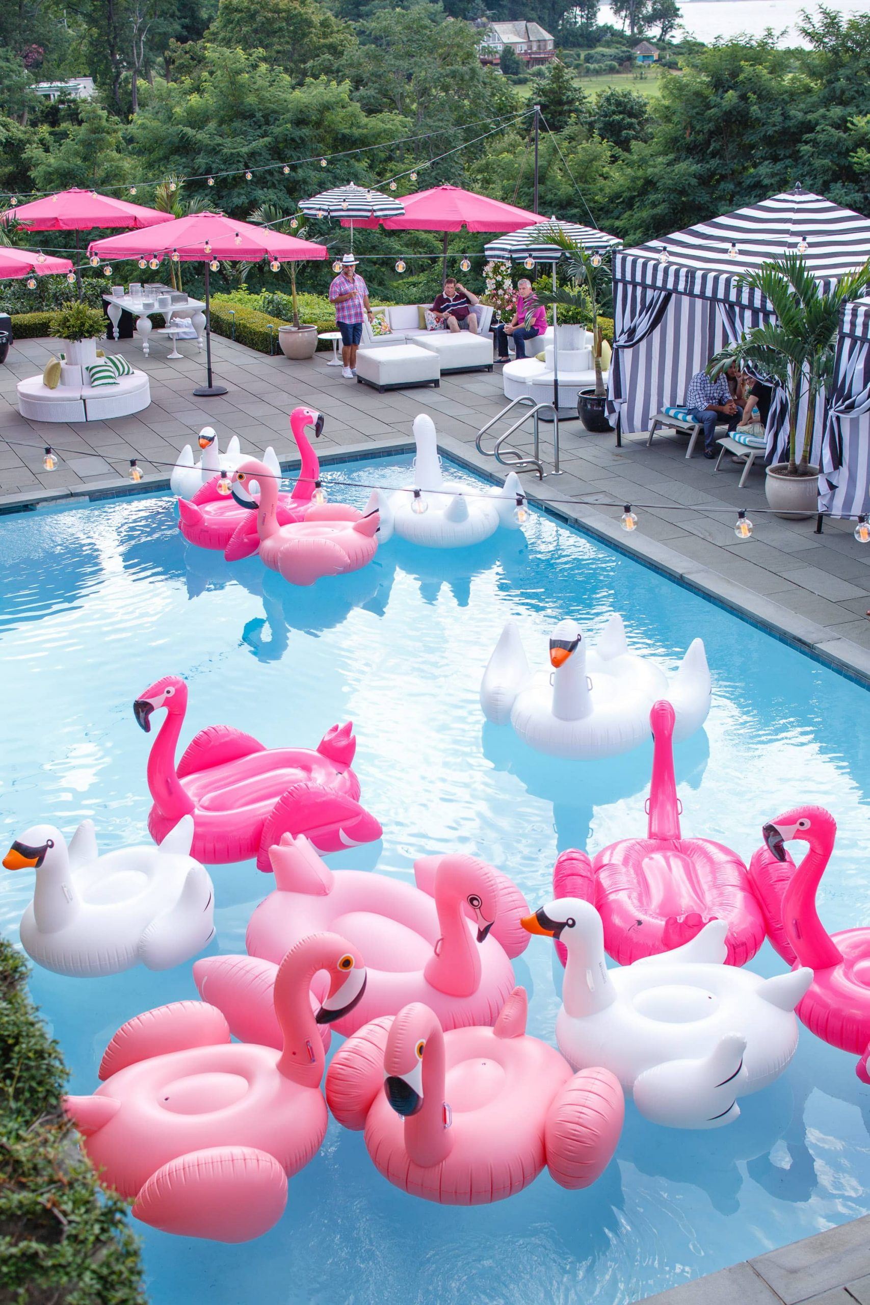 Pool filled with flamingo and swan floaties at this South Beach-inspired first birthday pool party in the Hamptons | Photo by Cava Photo