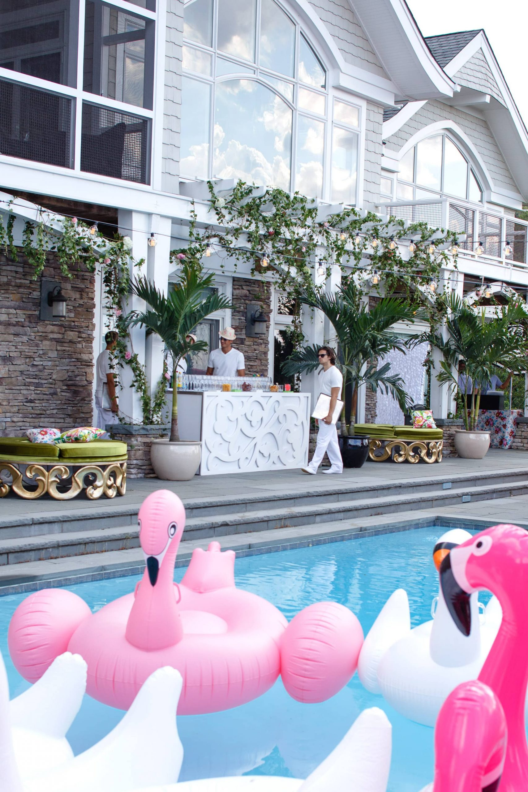 Drink bar and pool with pink flamingo and white swan floats at this South Beach-inspired first birthday pool party in the Hamptons | Photo by Cava Photo