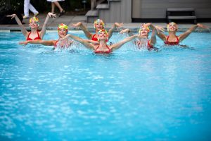Synchronized swimmers in red suits and colorful caps at this South Beach-inspired first birthday pool party in the Hamptons | Photo by Cava Photo