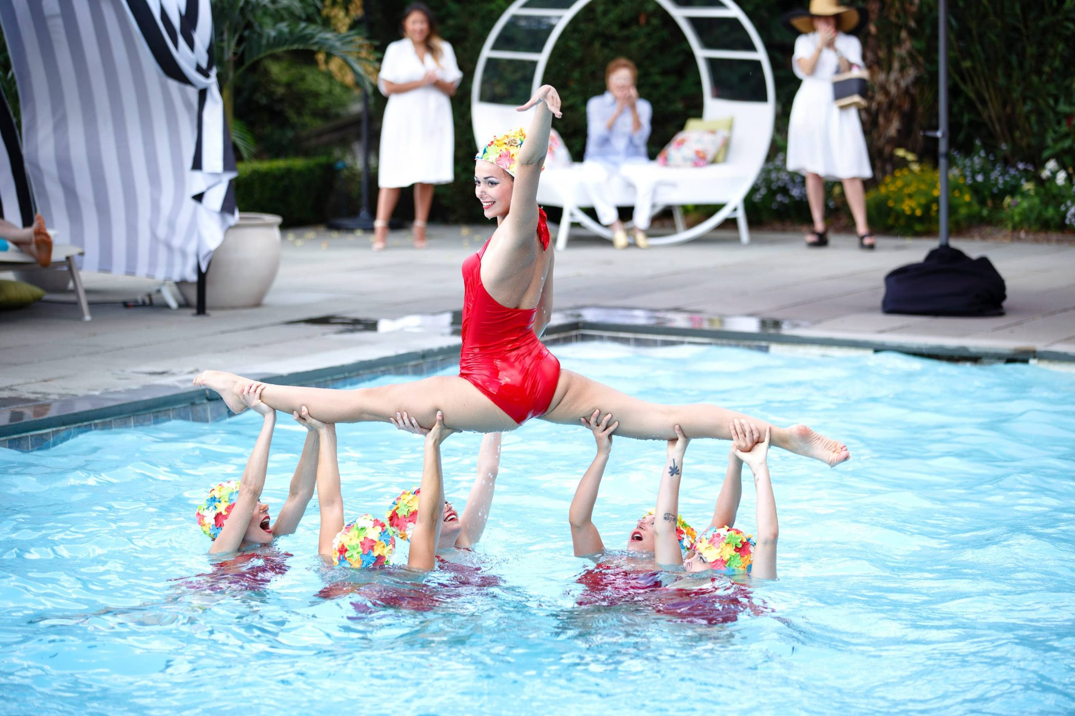 Synchronized swimmer doing a split in red suit and colorful cap at this South Beach-inspired first birthday pool party in the Hamptons | Photo by Cava Photo
