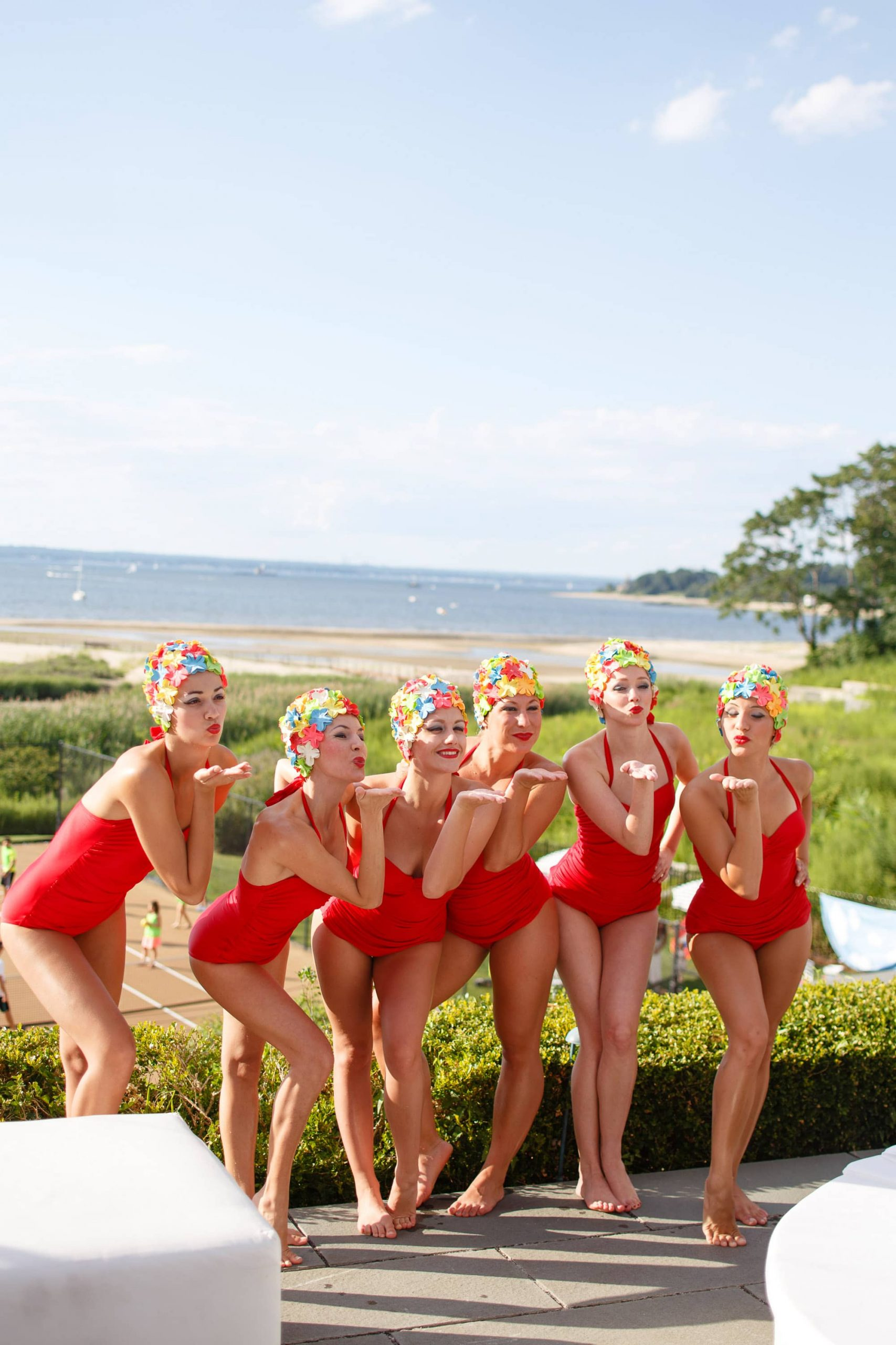 Synchronized swimmers in red suits and colorful caps blowing a kiss at this South Beach-inspired first birthday pool party in the Hamptons | Photo by Cava Photo
