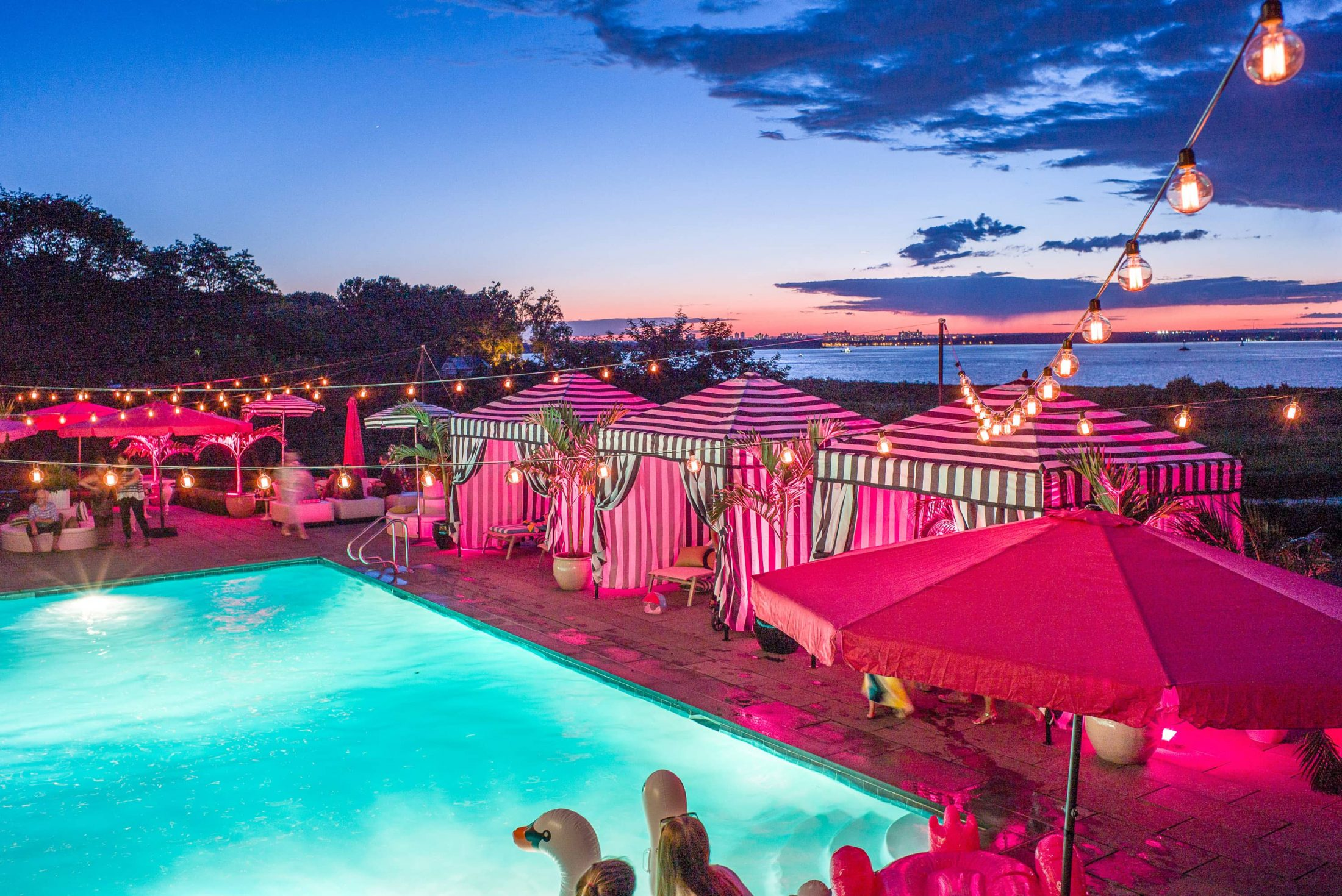Nighttime with pink lights to create a Saint Tropez theme at this first birthday pool party in the Hamptons | Photo by Cava Photo