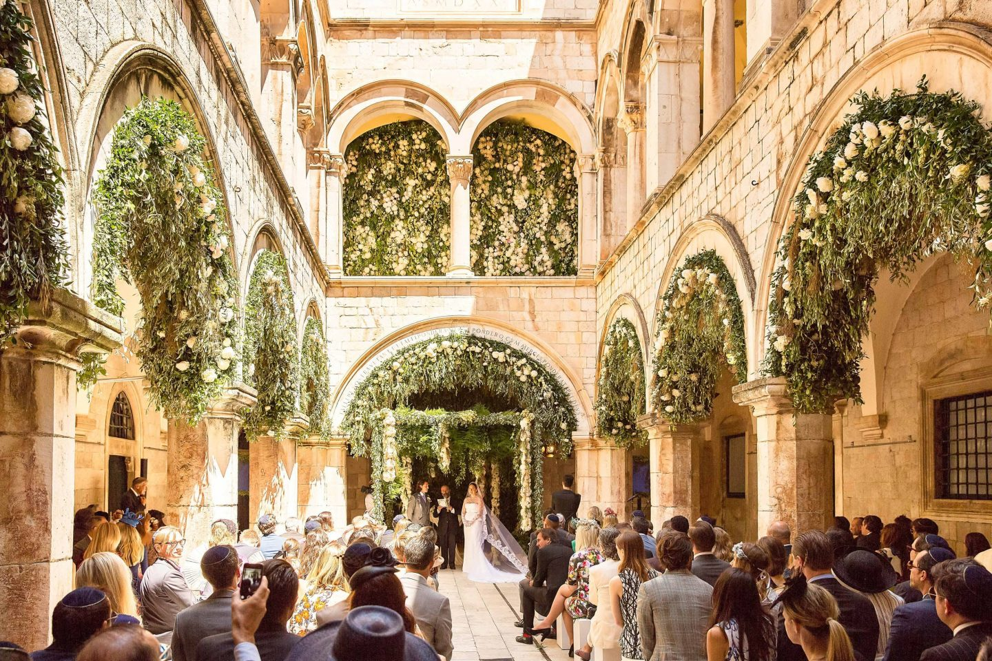 Bride and groom at ceremony decorated with peonies, jasmine, and tuberose by Theirry Boutemy at Palača Sponza at this Dubrovnik Wedding in Croatia | Photo by Robert Fairer