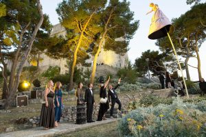 Guests and woman on stilts on their way to evening dinner at Fort Lovrijenac at this Dubrovnik wedding in Croatia | Photo by Robert Fairer