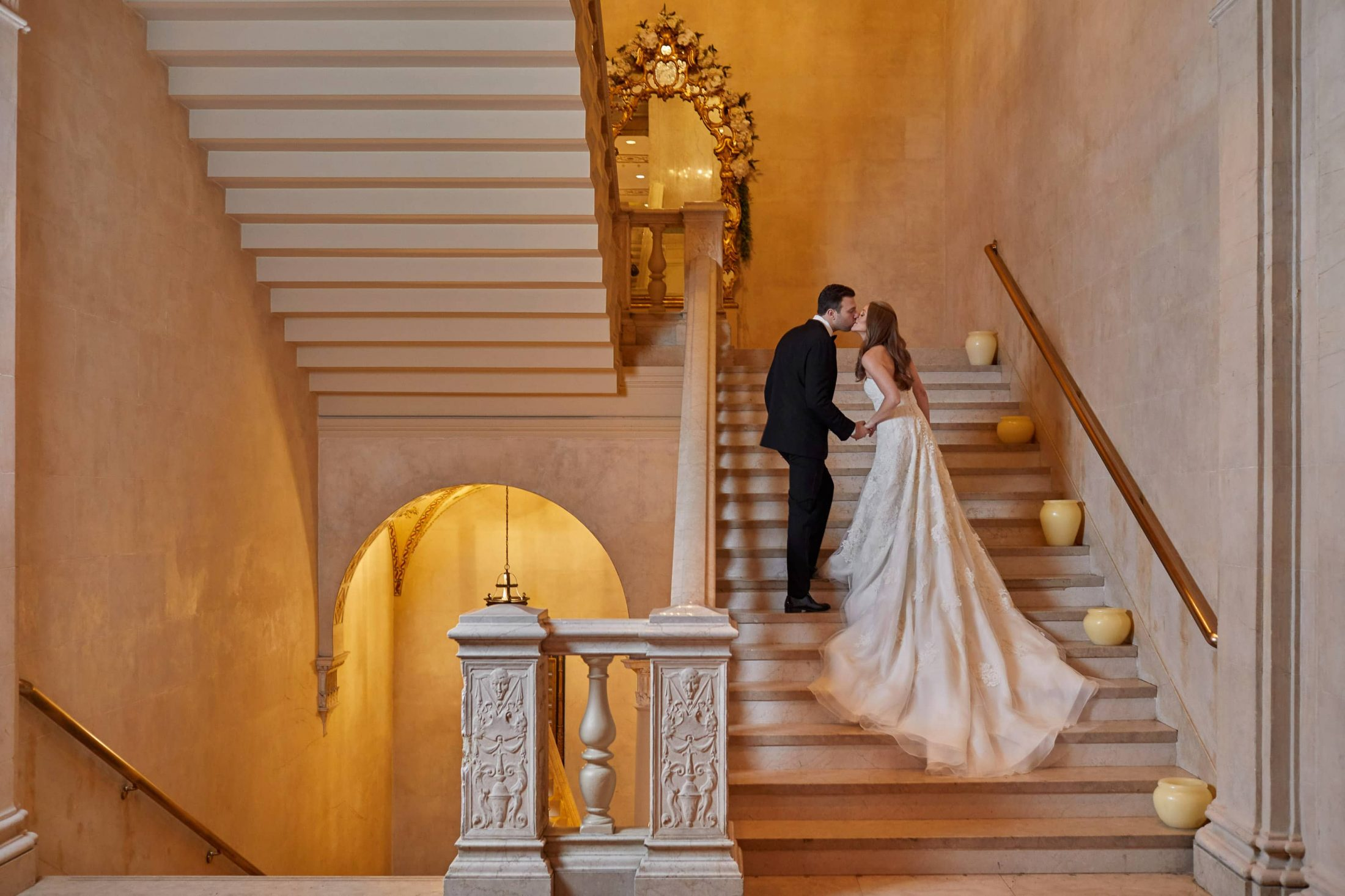 Bride and groom on the staircase at this classic autumn wedding at The Plaza in NYC | Photo by Christian Oth Studio