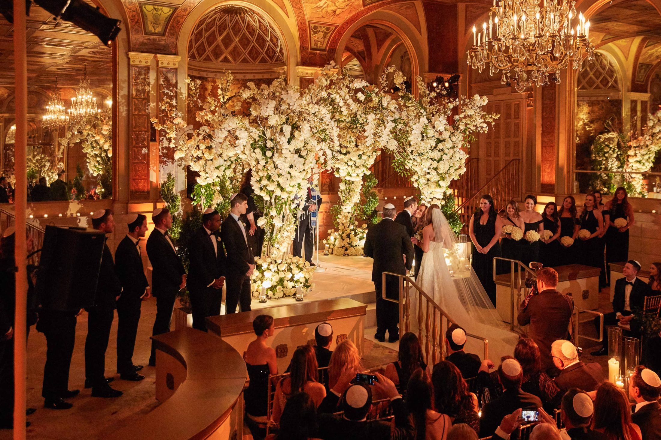 Bride and groom exchanging vows under gorgeous floral chuppah designed by Ed Libby at this classic autumn wedding at The Plaza in NYC | Photo by Christian Oth Studio