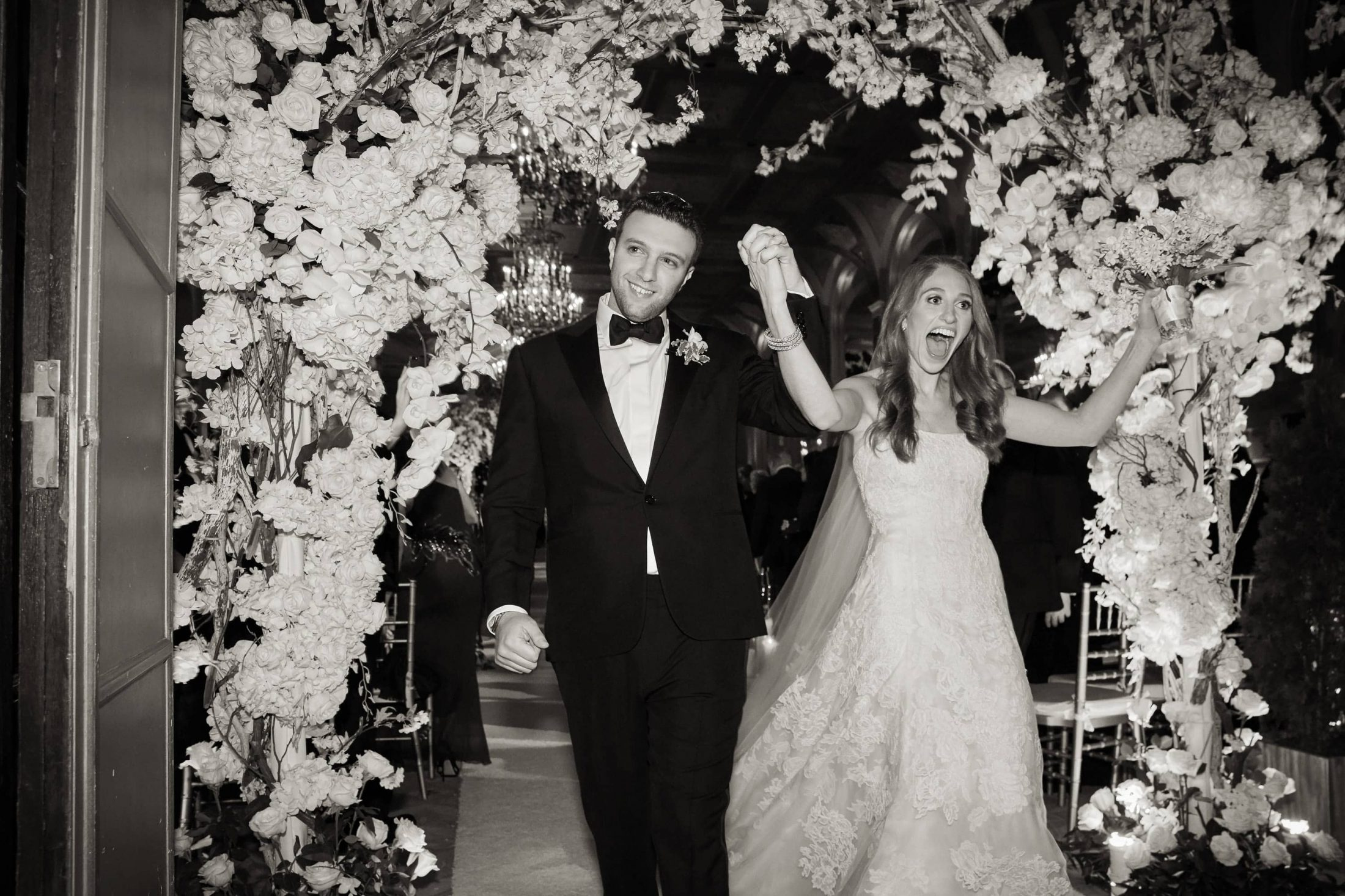 Newlyweds under floral arch designed by Ed Libby at this classic autumn wedding at The Plaza in NYC | Photo by Christian Oth Studio