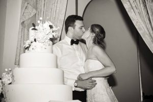 Bride and groom kiss by wedding cake at this classic autumn wedding at The Plaza in NYC | Photo by Christian Oth Studio