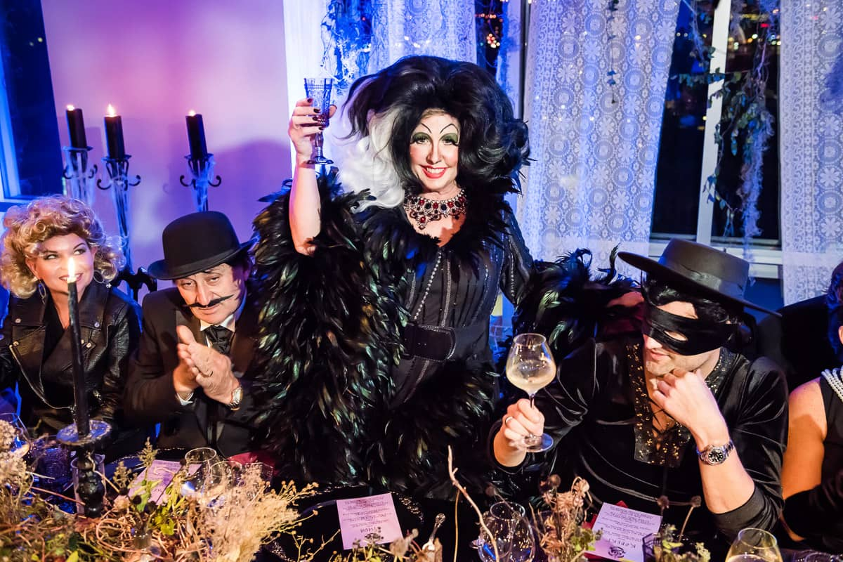 Cruella de Vil, seated with Zorro, a man in a bowler hat, and Sandy from Grease, making a toast at this epic halloween party at The Standard in NYC | Photo by Gruber Photographers