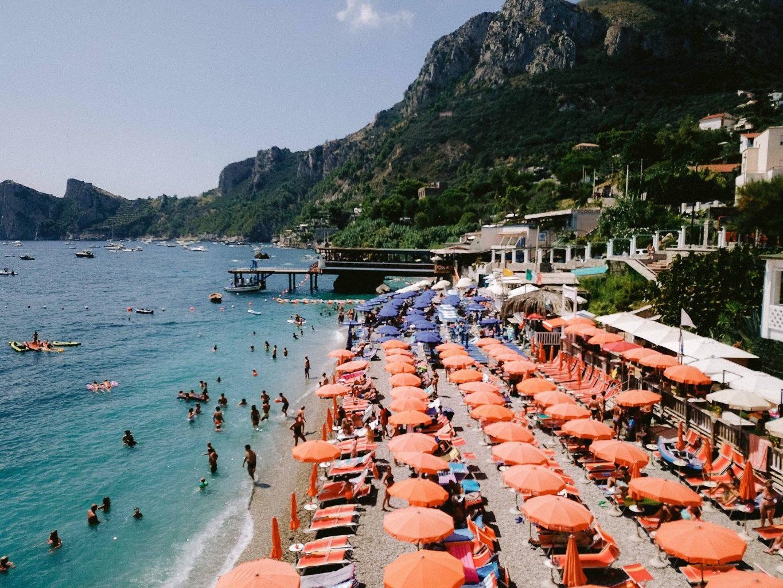 Orange beach umbrellas at this Amalfi Coast wedding weekend held Lo Scoglio | Photo by Allan Zepeda