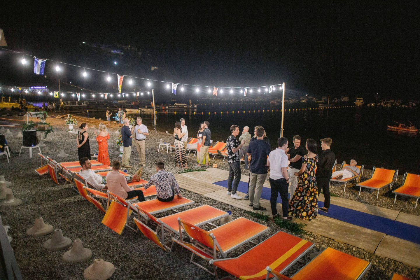 Guests on beach during evening pizza party at this Amalfi Coast wedding weekend held Lo Scoglio | Photo by Allan Zepeda