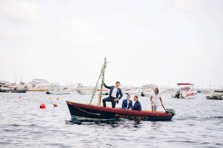 Groomsmen coming by boat at this Amalfi Coast wedding weekend held Lo Scoglio | Photo by Allan Zepeda