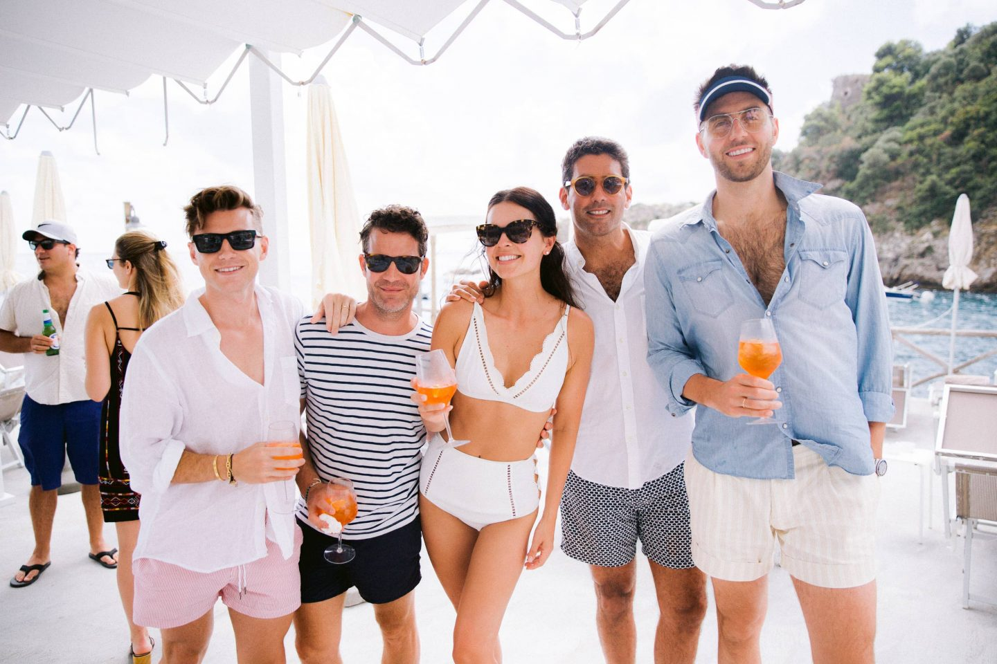 Bride and groom with guests and aperol spritzes during beach party near Conca del Sogno beach club at this Amalfi Coast wedding weekend held Lo Scoglio | Photo by Allan Zepeda