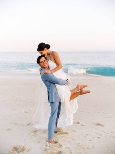 Groom picking up bride on the beach at this Los Cabos wedding in Mexico | Photo by Allan Zepeda
