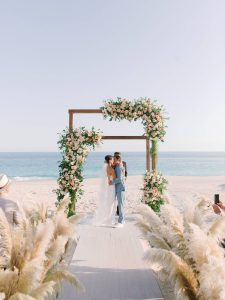 Bride and groom kiss at beach ceremony at this Los Cabos wedding in Mexico | Photo by Allan Zepeda