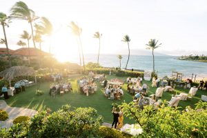 Guests at reception during sunset overlooking the Pacific Ocean at Maui wedding at Four Seasons Resort Maui in Wailea, Hawaii | Photo by James x Schulze