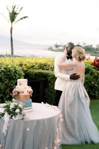 Bride and groom kiss in front of wedding cake at Maui wedding at Four Seasons Resort Maui in Wailea, Hawaii | Photo by James x Schulze