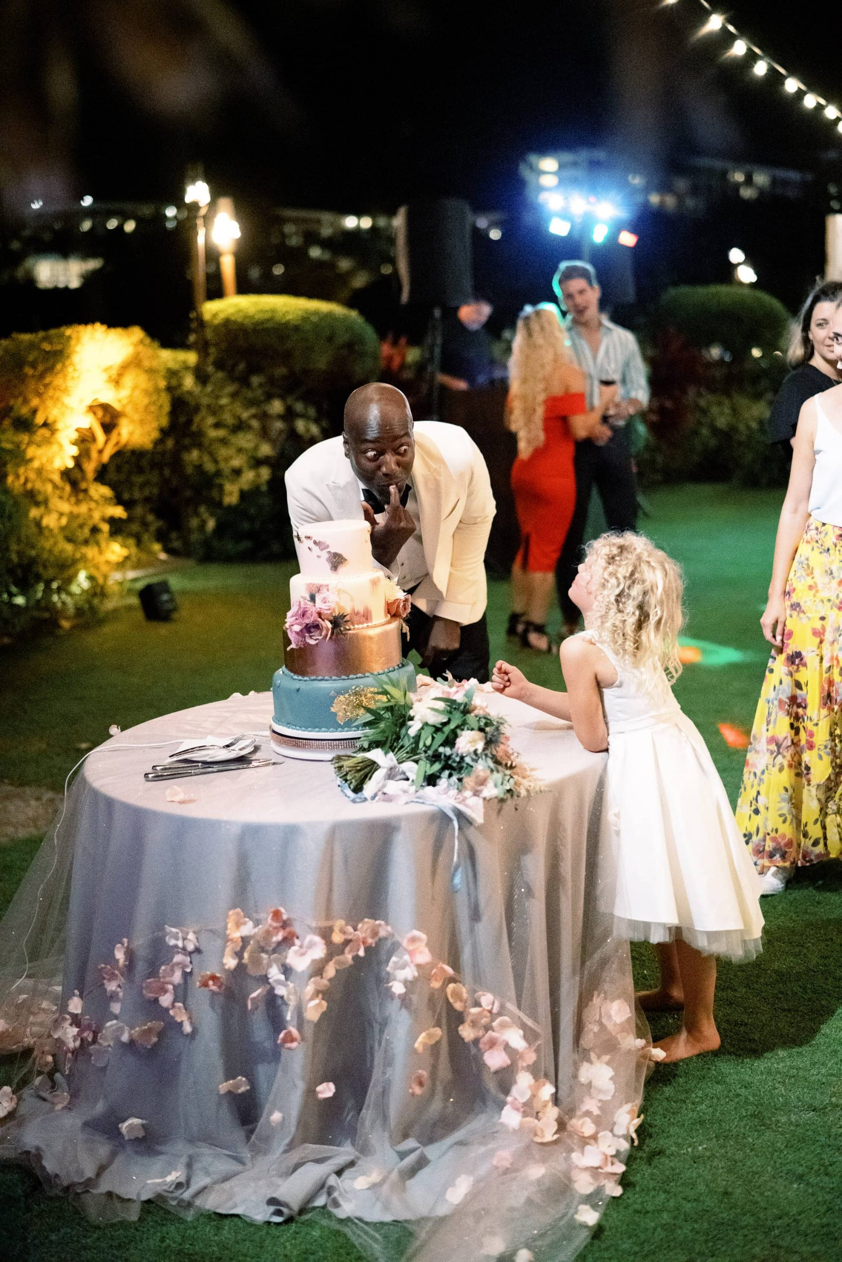 Groom acting goofy with flower girl and cake during reception at Maui wedding at Four Seasons Resort Maui in Wailea, Hawaii | Photo by James x Schulze