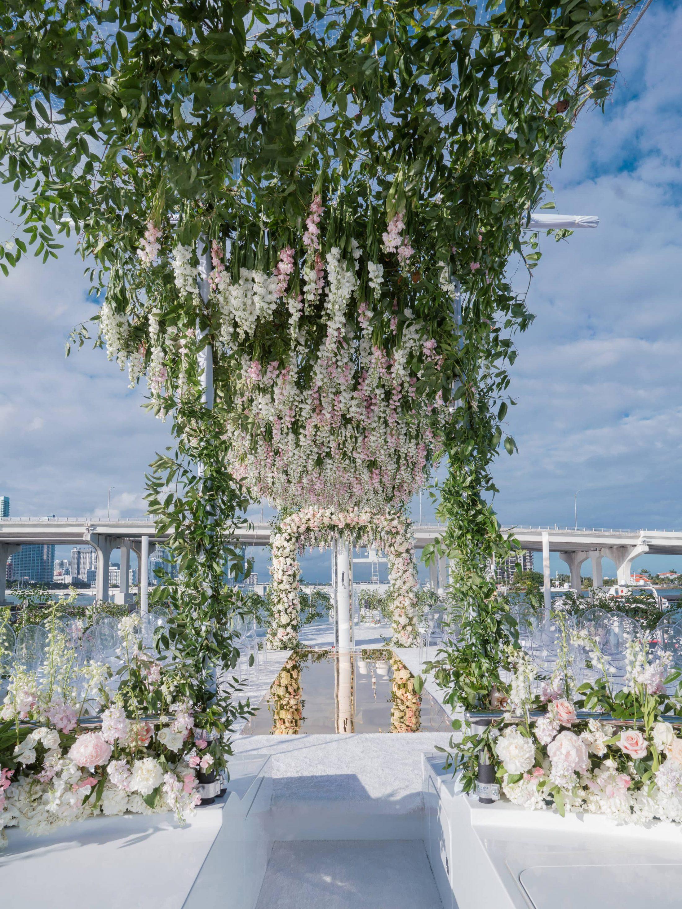 Glamorous aisle underneath cascading flowers at this Miami yacht wedding | Photo by Corbin Gurkin