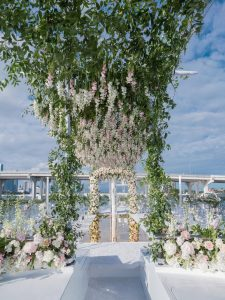 Glamorous aisle underneath cascading flowers at this Miami yacht wedding | Photo by Corbin Gurkin