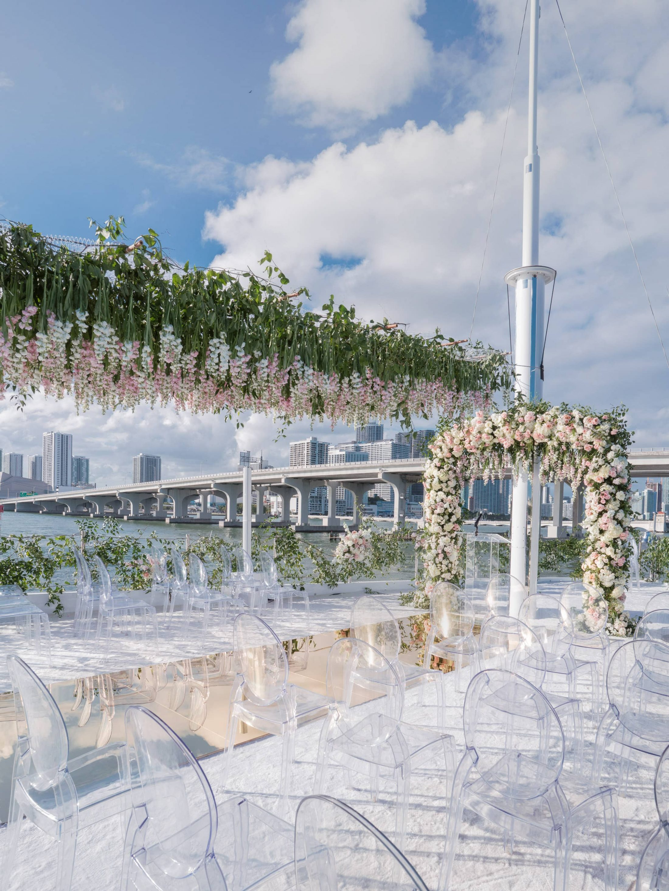 Aisle under cascading flowers and lucite chairs for at this Miami yacht wedding | Photo by Corbin Gurkin