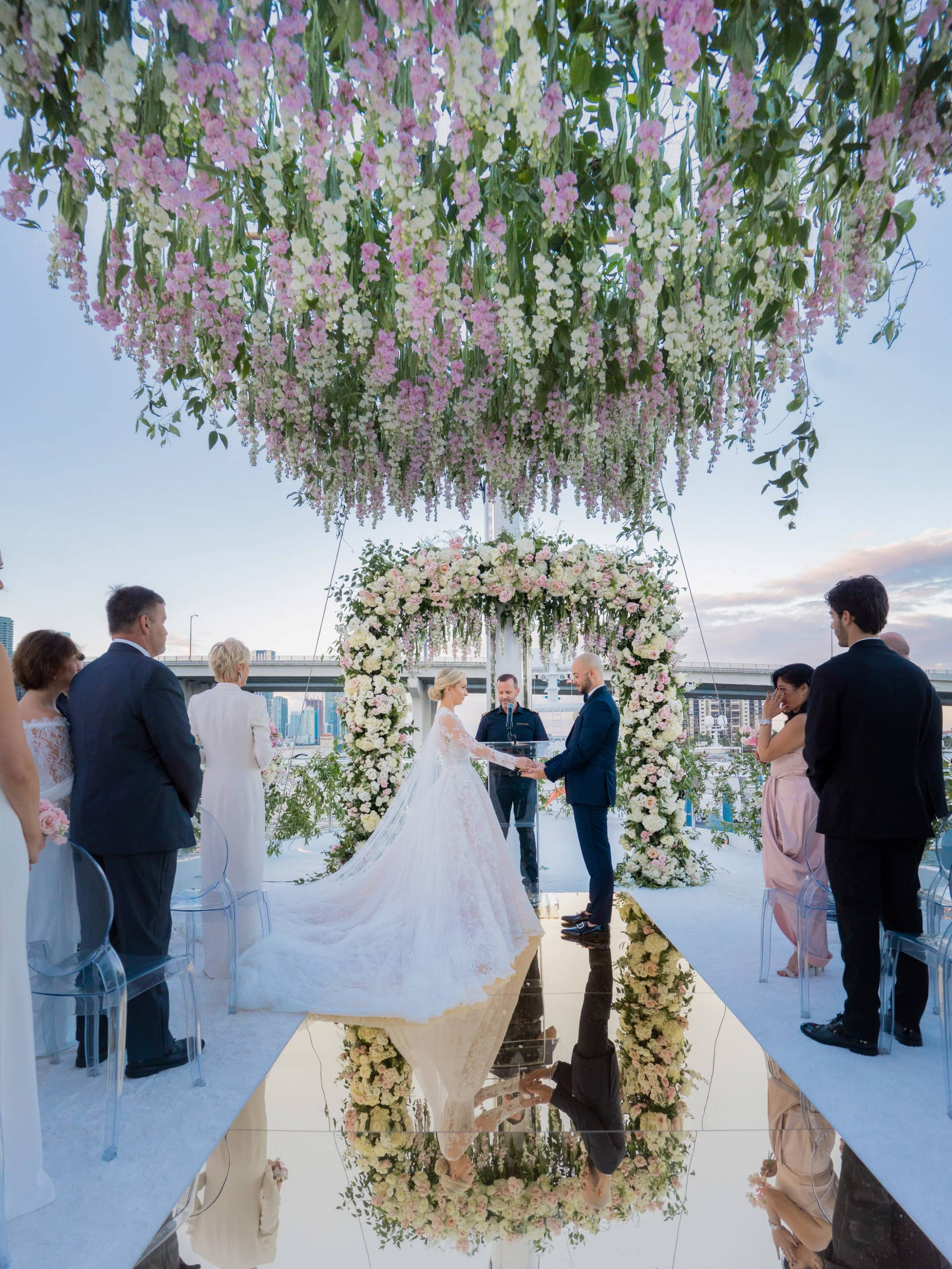 Bride and groom exchanging vows underneath cascading flowers at this Miami yacht wedding | Photo by Corbin Gurkin
