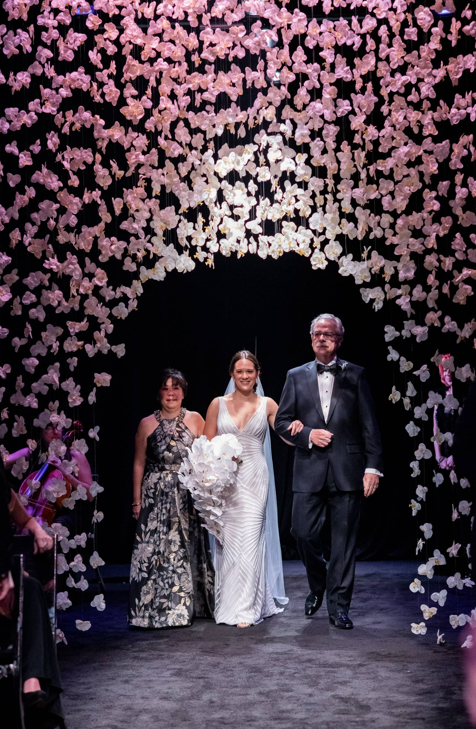 Bride entrance under hanging white orchards during ceremony at this NYE wedding in New York City | Photo by Gruber Photo
