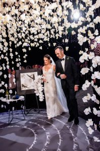 Bride and groom entering the chuppah made of hanging white orchards at this NYE wedding in New York City | Photo by Gruber Photo