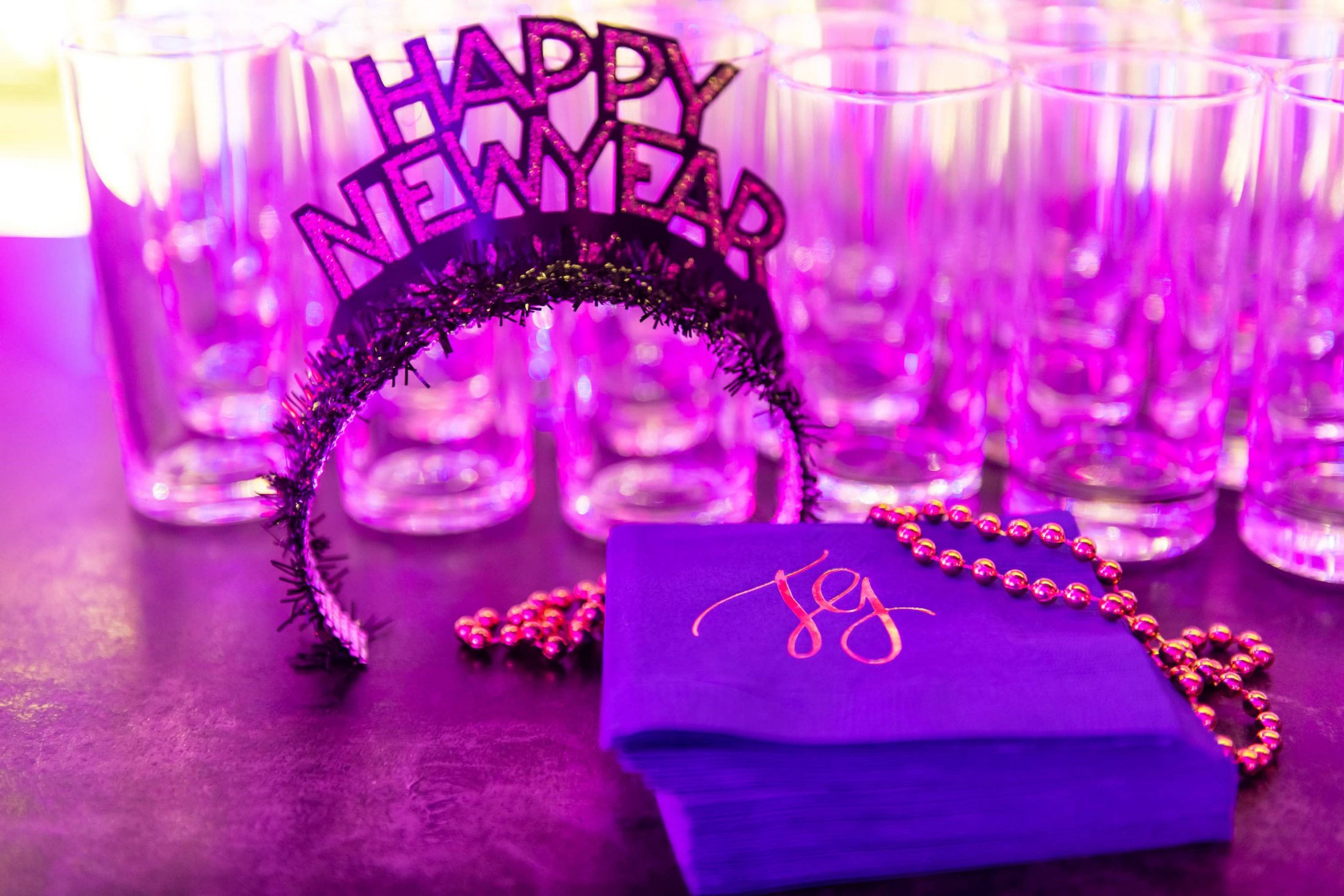 Happy New Year hat with gold necklace and monogrammed blue napkins at champagne bottle-inspired reception at this NYE wedding in New York City | Photo by Gruber Photo