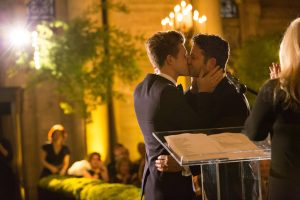 Grooms kiss during ceremony at this New York Public Library wedding | Photo by Genevieve de Manio