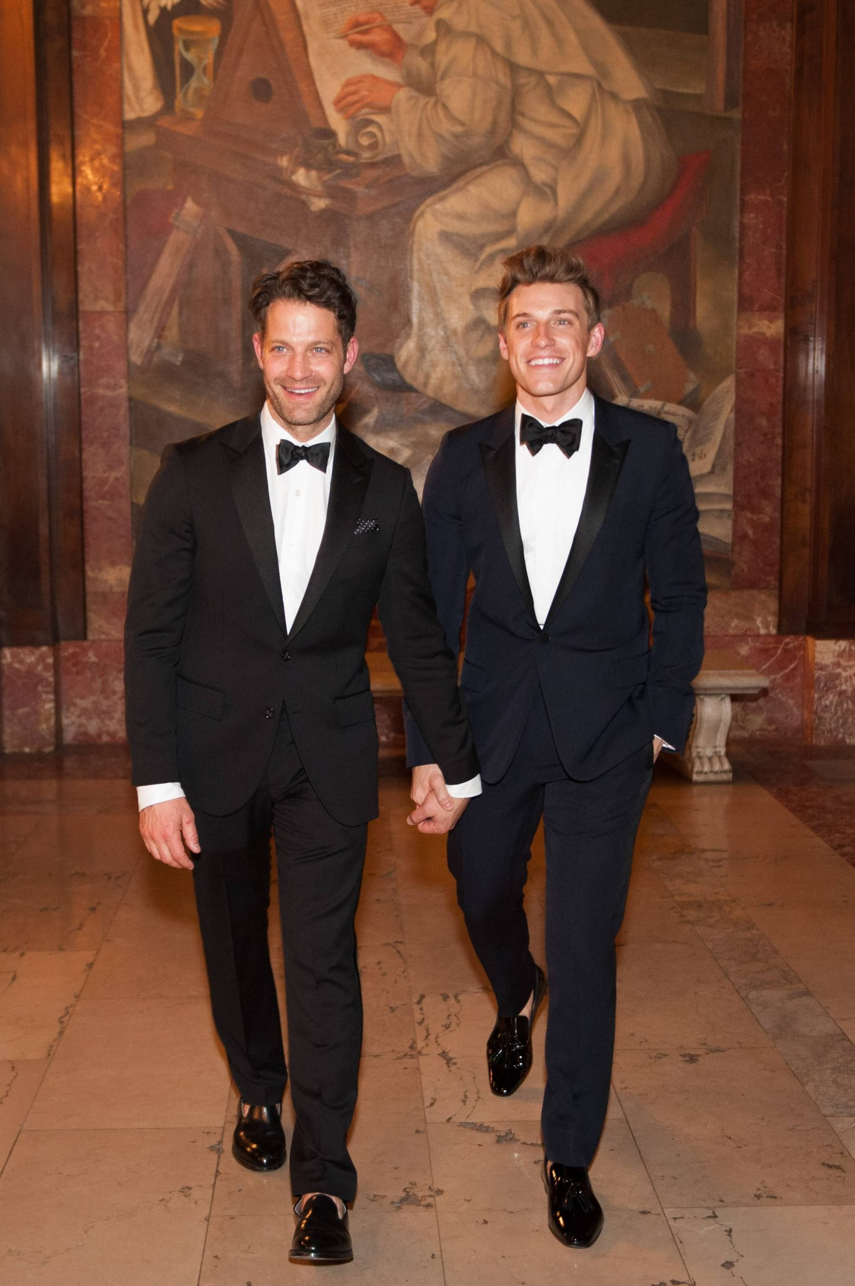 Grooms smiling in black tuxedos with black bowties at this New York Public Library wedding | Photo by Genevieve de Manio