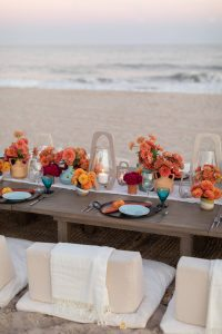 Table decor with orange flower decor at 40th birthday dinner on the beach in Southampton | Photo by Luis Zepeda