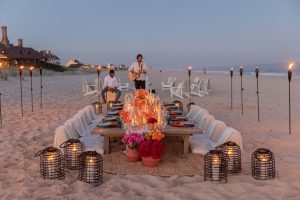 Table set up with entertainment at 40th birthday dinner on the beach in Southampton | Photo by Luis Zepeda