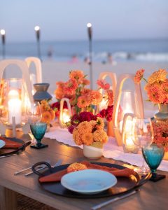 Night falling table set-up with candles at 40th birthday dinner on the beach in Southampton | Photo by Luis Zepeda