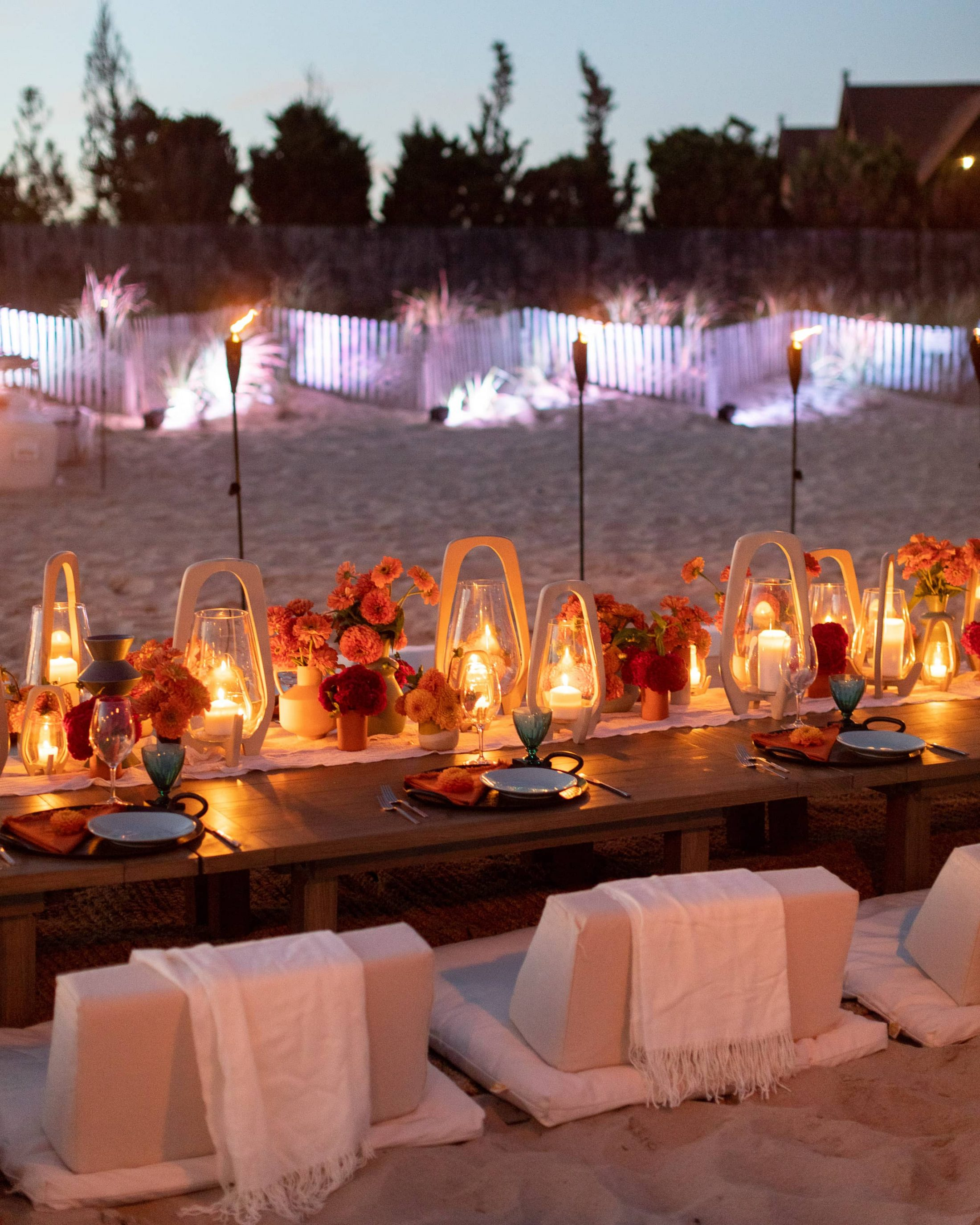 Table set-up at night at 40th birthday dinner on the beach in Southampton | Photo by Luis Zepeda